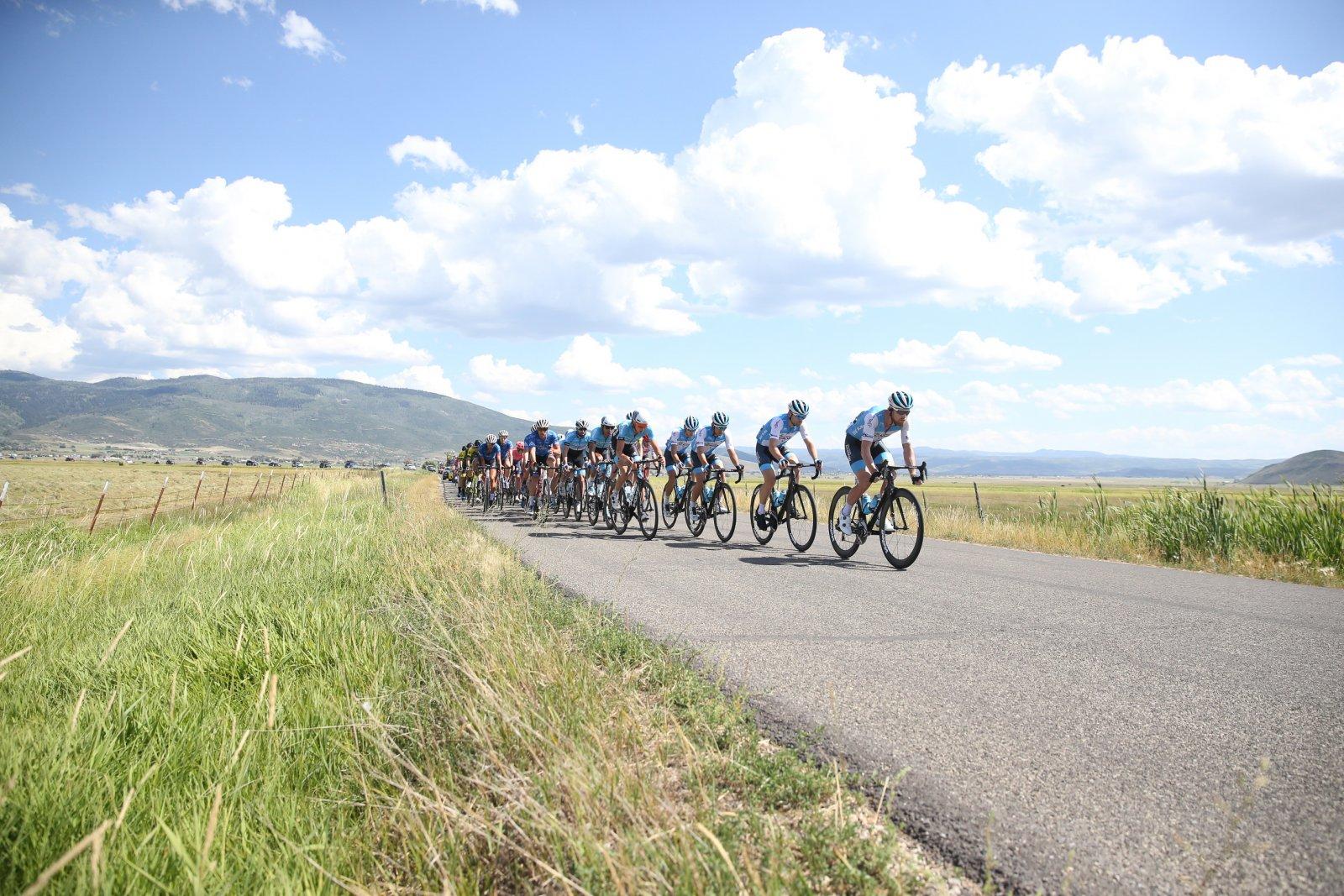 The peloton charges through beautiful farmland.