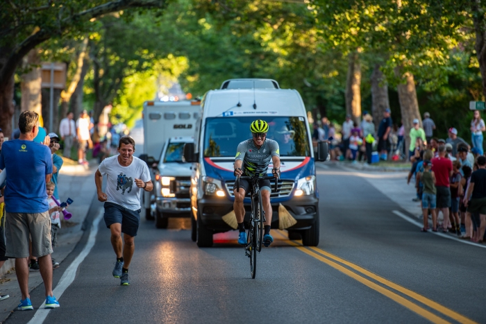 "Miguel Bryon (Arapahoe-Hincapie p/b BMC) ""races"" a runner up State Street while holding a wheelie. Stage 4, 2019 Tour of Utah. Photo by Steven L. Sheffield"