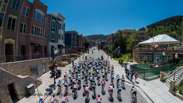 The peloton rolls up Main Street Park City  during the neutralized start of Stage 6, 2019 LHM Tour of Utah (Photo by Dave Richards, daverphoto.com)