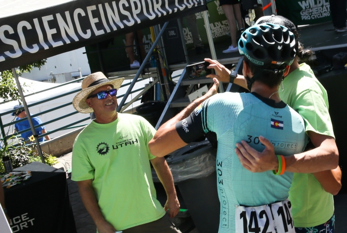 Antonio Baca takes a selfie with a volunteer at sign in. He wins America First Credit Union Fan Favorite Jersey after the final stage.
