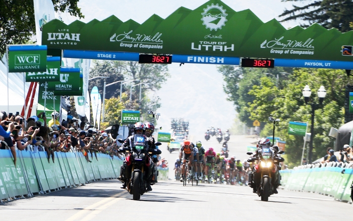 The peloton races through the Payson Start/Finish. 2018 Tour of Utah Stage 2, August 8, 2018, Payson, Utah. Photo by Cathy Fegan-Kim, cottonsoxphotography.net