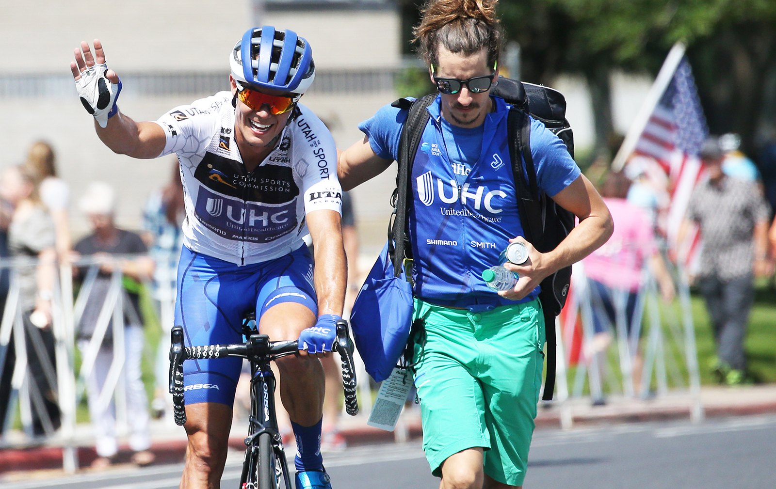 UHC soigneur escorts Travis McCabe to the green room. 2018 Tour of Utah Stage 3, August 8, 2018, Layton, Utah. Photo by Cathy Fegan-Kim, cottonsoxphotography.net