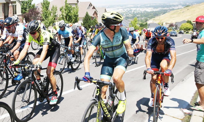 Isaiah Newkirk of the 303 Project looks back to say hey to Hangar 15 rider, Cortlan Brown.  2018 Tour of Utah Stage 3, August 8, 2018, Layton, Utah. Photo by Cathy Fegan-Kim, cottonsoxphotography.net