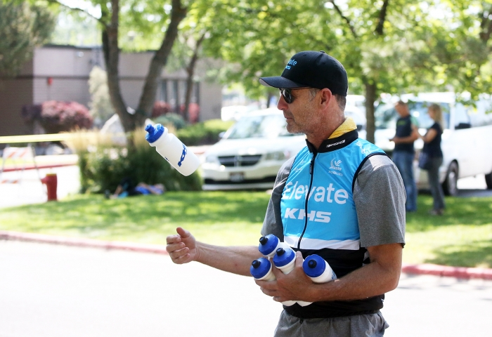 Elevate soigneur waits for the peloton to go through the 5 laps in Layton. 2018 Tour of Utah Stage 3, August 8, 2018, Layton, Utah. Photo by Cathy Fegan-Kim, cottonsoxphotography.net