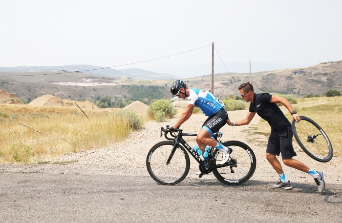 Mechanic gives a rider a push after fixing a mechanical.  Stage 5 of the 2018 Tour of Utah, August 10, 2018. Photo by Cathy Fegan-Kim, www.cottonsoxphotography.net