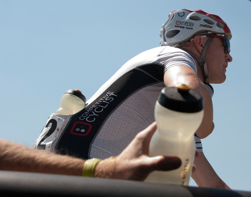 Tommy Nankervis takes a feed from the Competitive Cyclist Team Car.