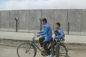 Afghanistan kids ride by wire fence on bicycle