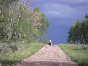 Ashley chugging up a classic Great Divide road with a thunderstorm