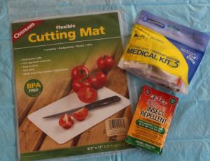 Coghlan's cutting board, Adventure Medical Kit, and BugBand allnatural,