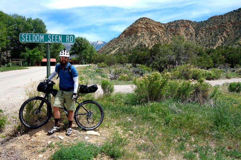 Ty Hopkins riding on 2 Mile Road with the La Sals in the background. La Sal Peak is on the right.