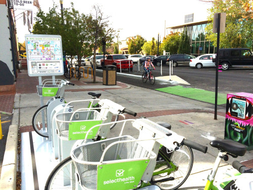 A rider enjoys the brand new 300 S. Protected Bike Lane in Salt Lake City, Utah. Salt Lake City's bike share, the Squatter's bike corral, and bike racks are all on display in this image. Photo by Dave Iltis
