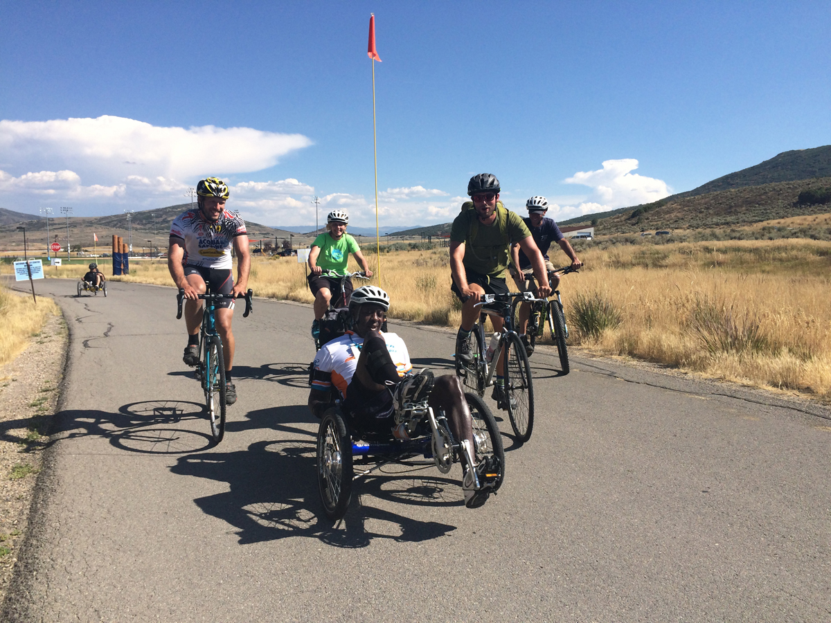 Michael Ray finishing the 52 mile course at the 2016 Summit Challenge surrounded by his ride companions. Reid Wycoff of the National Ability Center is in the white jersey. Ray hopes to cut his time down to 6 hours for 2017. Photo by Dave Iltis