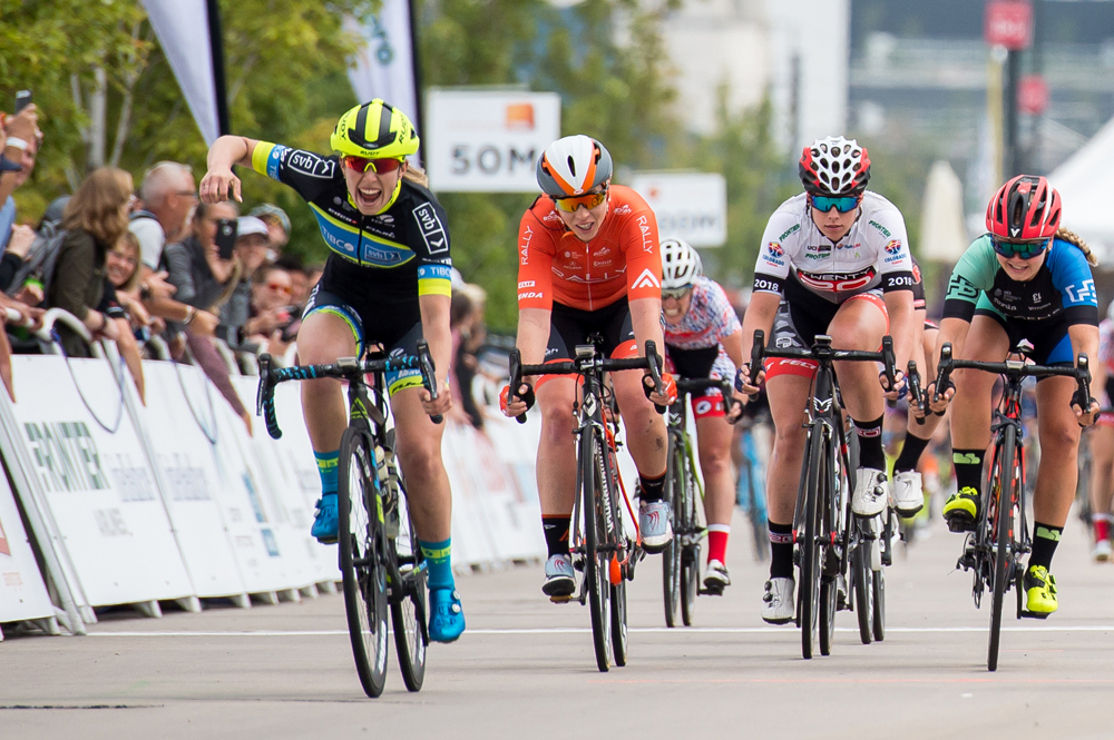 Jennifer Valente (Twenty20 p/b Sho-Air) raises her arm in victory after winning the bunch sprint to take Women's Stage Four, a 4 lap circuit race around downtown Denver. 2018 Colorado Classic cycling race (Photo by Dave Richards, daverphoto.com