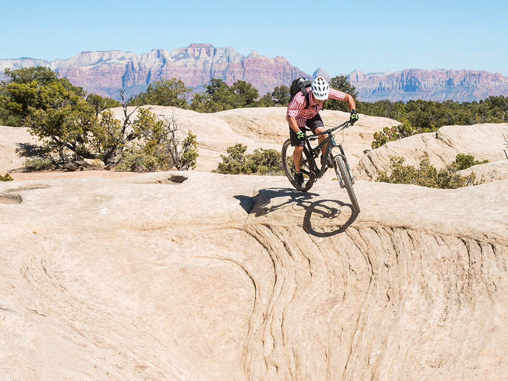 A certified IMBA Epic, the Gooseberry Mesa trail system is a must-do, classic ride. In this photo, Park City resident, Todd Winzenried, drops in on a slickrock halfpipe on Gooseberry's North Rim Trail, with the cliffs of Zion National Park in the background. Photo by John Shafer/Photo-John.net