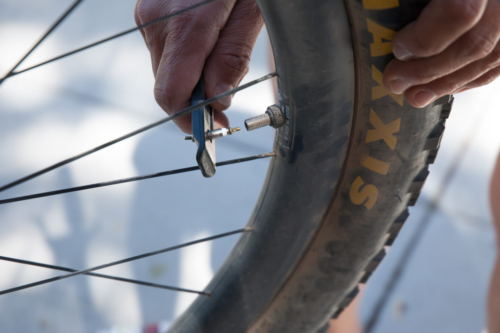 Removing the valve core with the Snēk Cycling Lifeboat Tire Lever.
