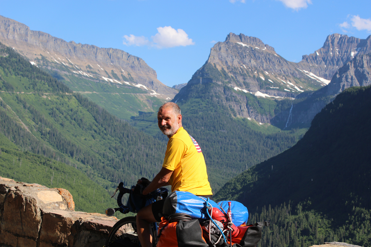 Lou at the location that inspired the Monte Dolack painting, Going to the Sun Highway, Glacier National Park.