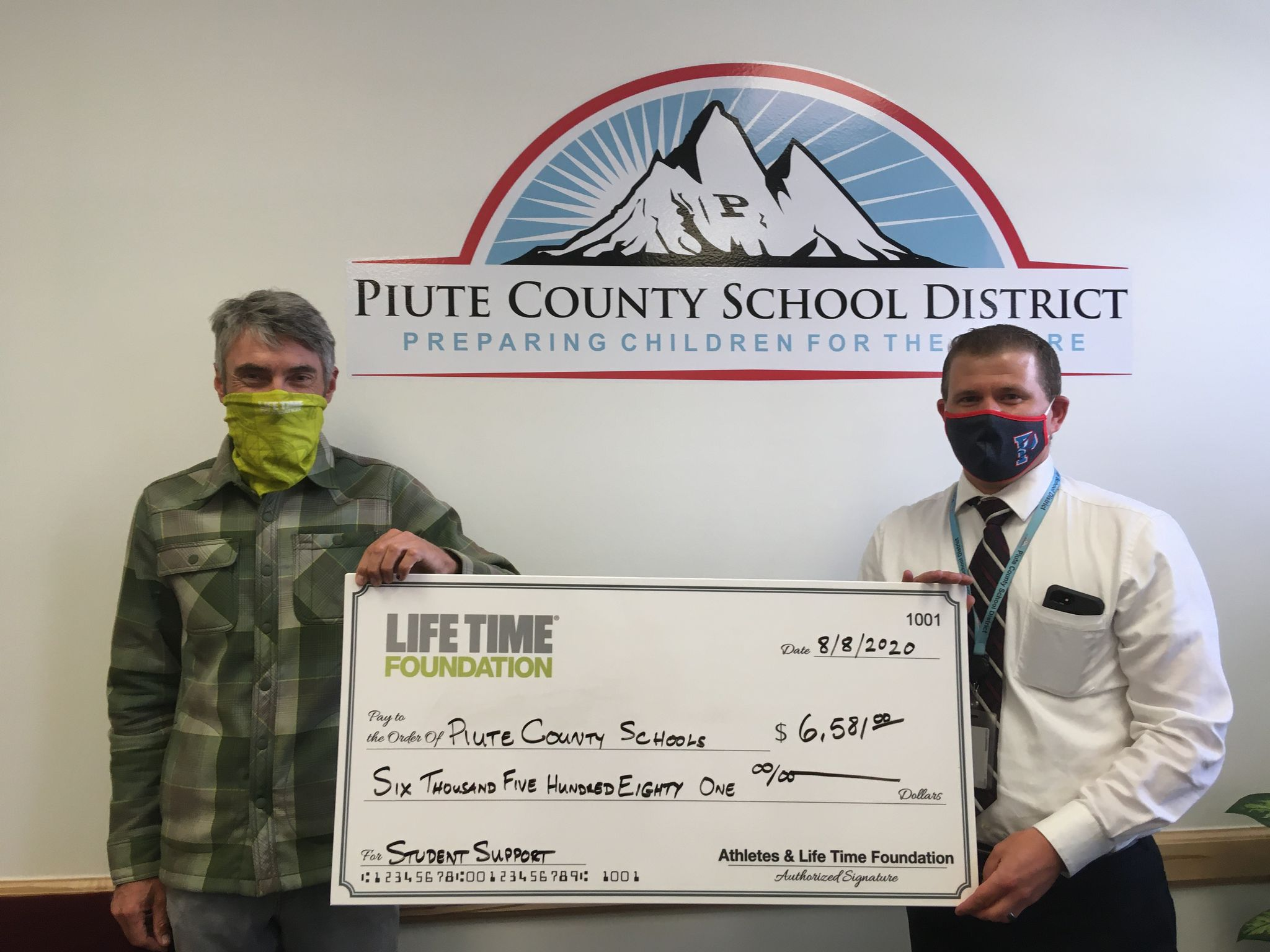 Burke Swindlehurst, event director of Life Time's Crusher in the Tushar, presents the Piute County School District with a check for $6581.00. Photo courtesy Life Time Events