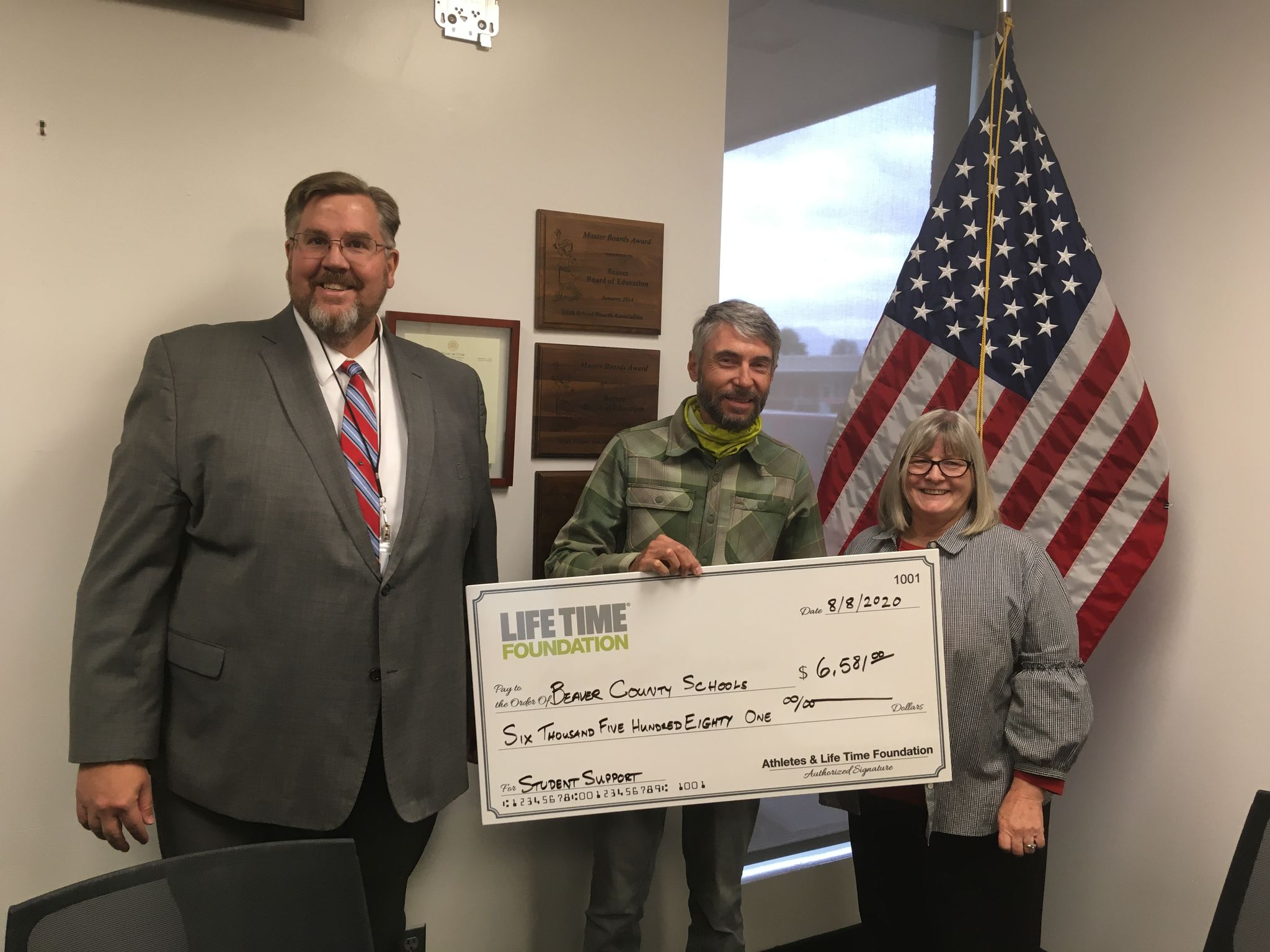 Burke Swindlehurst, event director of Life Time's Crusher in the Tushar, presents the Beaver County School District with a check for $6581.00. Photo courtesy Life Time Events