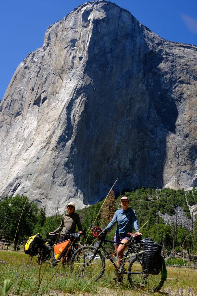 Rain (left) and Clara stand with their bikes in the meadows below El Capitan at the end of their bikepacking journey. Photo by Clay James